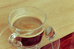 Black expresso coffee in small glass cup on wooden table with te Stock Photos