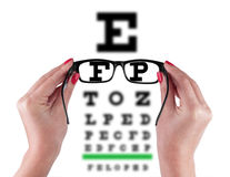 Black Eye Glasses in women`s hand. Isolated on eyesight test chart background royalty free stock image