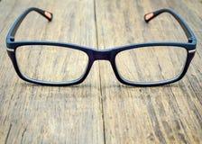 Black eye glasses on wooden floor Royalty Free Stock Photography