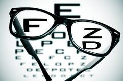 Black eyeglasses. Eyeglasses over a blurry eye chart Royalty Free Stock Photography