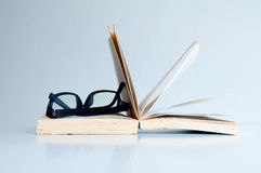 Black eyeglasses on the opened book Royalty Free Stock Photos