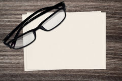 Black eyeglasses and paper on wood background royalty free stock photography