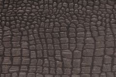 Black fabric with crocodile pattern. Fashionable textured backgrounds Royalty Free Stock Photo