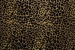 Black fabric with golden leopard fur print. Black fabric with metallic golden leopard fur print. Retro fashion background stock photography