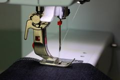 Presser foot of a sewing machine with dark fabric stock photos