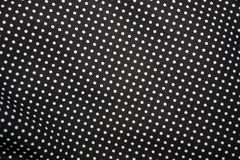 Black fabric and white tiny polka dot background, close-up stock photography