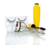 Black false eyelashes, mascara and hair curlers isolated on white. Royalty Free Stock Photography