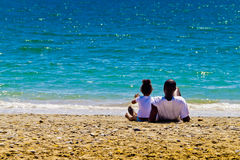 Black family and azure sea. Father and daughter sit on the beach and look at azure sea Royalty Free Stock Image