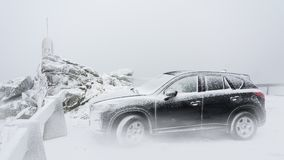 Black family car on a snowy mountain peak. Frosty wintry scene with the sport utility vehicle standing inside a cloud on the mountain top Royalty Free Stock Photography