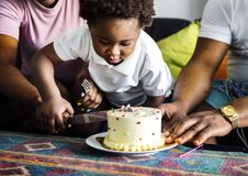 Black family cutting birthday cake stock photos
