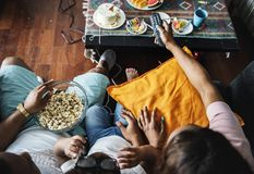 Black family eating popcorn while watching movie at home Royalty Free Stock Images