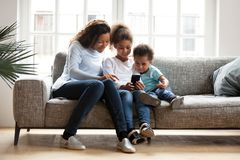 Mother and two kids together with laptop on couch royalty free stock image