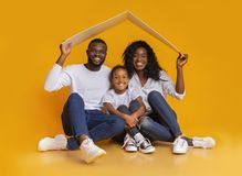 Free Black Family Sitting Under Symbolic Roof Dreaming Of New Home. Royalty Free Stock Image - 161187066