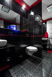 Black is always in fashion... Interior of a stylish bathroom with black tiles, mirror, white sink and toilet Royalty Free Stock Photography