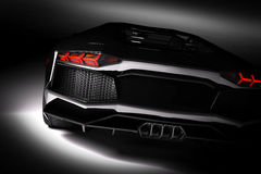 Black fast sports car in spotlight, black background. Shiny, new, luxurious. Stock Images