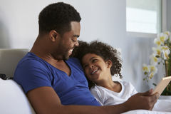 Black father and daughter relaxing in bed look at each other Stock Photography