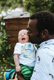 Black father kissing his mixed race baby boy stock photo