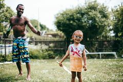 Black father playing with his son outside. Black father playing with his mixed race son outside on a summers day royalty free stock photos