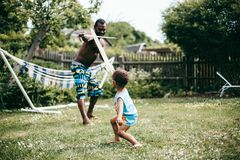 Black father playing with his son outside on a summers day stock photos