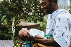 Black father smiles of joy while holding his baby boy stock image