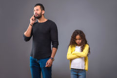 Black father talking on his phone while his daughter waiting. A black father talking on his phone while his young daughter restlessly waiting for him with her Royalty Free Stock Photo