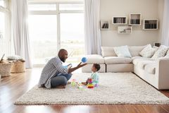 Black father and toddler son playing in sitting room stock photos