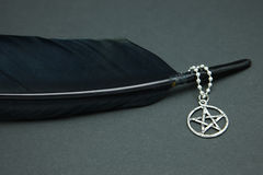 Black feather quill and pentacle necklace Royalty Free Stock Image