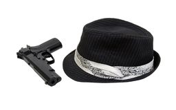 Black Fedora and gun. Black pinstriped Fedora hat with white band and hand gun - path included royalty free stock images