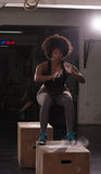 Black female athlete is performing box jumps at gym Royalty Free Stock Images