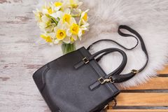 Black female bag on white fur, a bouquet of daffodils. Fashionable concept Royalty Free Stock Images