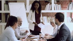 Black female boss give papers to employees group at meeting