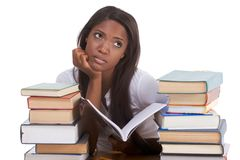 Black female college student by stack of books. High school or college ethnic student girl sitting by the desk with lot of books in class or library and doing Stock Image