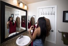 Woman Trying on clothes Looking at Mirror in Bathroom. Black female deciding between dresses and thinking about choosing a stylish fashion to wear.  She is Royalty Free Stock Photo