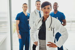 Black female doctor leading medical team. Black female doctor in charge at hospital, leading medical team om doctors and surgeons royalty free stock image