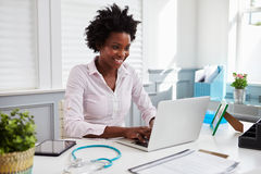 Black female doctor at work in office using laptop computer royalty free stock images