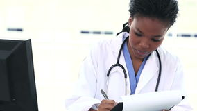 Black female doctor writing on a clipboard Royalty Free Stock Image