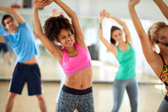 Black female doing stretching exercises in group Royalty Free Stock Photos