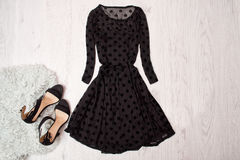 Black female dress with long sleeves and black shoes on a wooden background. Fashionable concept, top view royalty free stock images