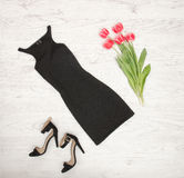 Black female dress, shoes and pink tulips on a wooden background. Fashionable concept Royalty Free Stock Photos
