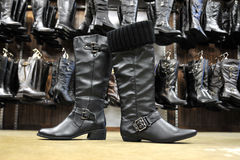 Black female leather boots. Two different female leather boots in front of a wall full of female leather boots Stock Image