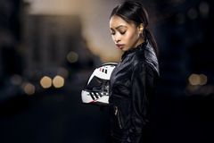 Female Motorcycle Rider on a Street. Black female motorcycle rider or race car driver wearing a racing helmet and leather jacket. Part of the gritty woman series royalty free stock photography