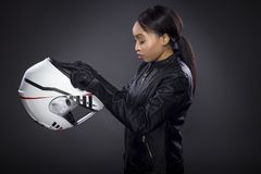Female Motorcycle Rider or Racer with Helmet. Black female motorcycle rider or race car driver wearing a racing helmet and leather jacket. Part of the gritty stock photo
