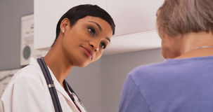 Black female radiologist discussing x-ray results with mature fe. A young doctor consults with a senior patient Stock Photography