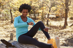 Black female runner sitting in a forest checking smartwatch Royalty Free Stock Image