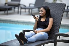 Female on a Vacation using a Voice Assistant on a Smart Phone. Black female on a speaker phone call in a hotel resort.  She is working while on vacation or Stock Photos