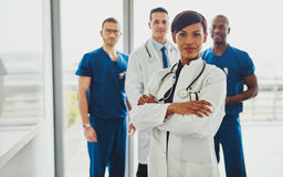 Black female standing in front of team Stock Images