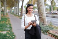 Black female student walking with tablet near street with trees. royalty free stock images
