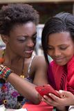 Black Female students looking on a cellphone stock photography
