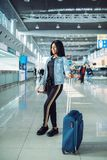 Black female tourist in international airport. Black female tourist with suitcase and phone waiting for departure in international airport. Passenger with royalty free stock image