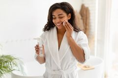 Free Black Female Using Cotton Pad And Micellar Water In Bathroom Royalty Free Stock Images - 220839629